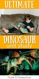 Boy reading a book about Dinosaurs and a big animatronic dinosaur.