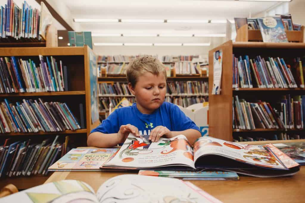 A boy looking at a book at the library with shelves of books beside and behind him.