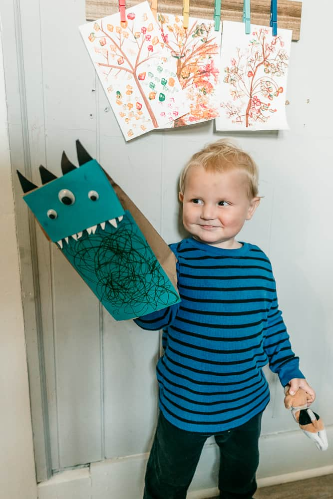 Little boy playing with paper bag monster puppet