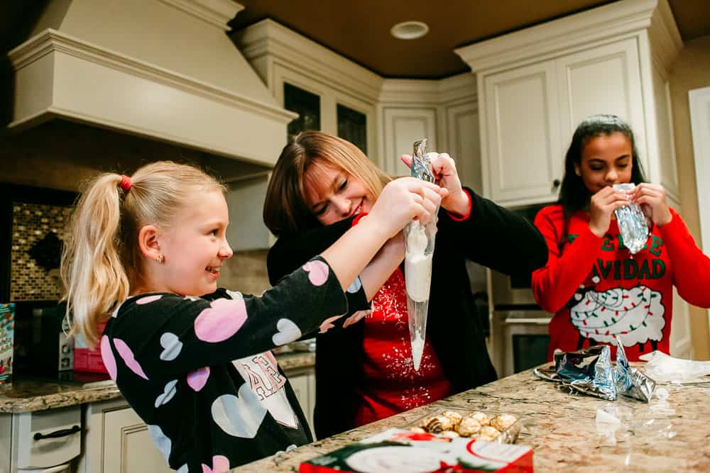 Woman helping girl with icing to decorate gingerbread houses