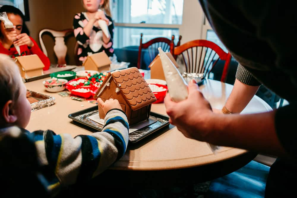 kid decorating a gingerbread house