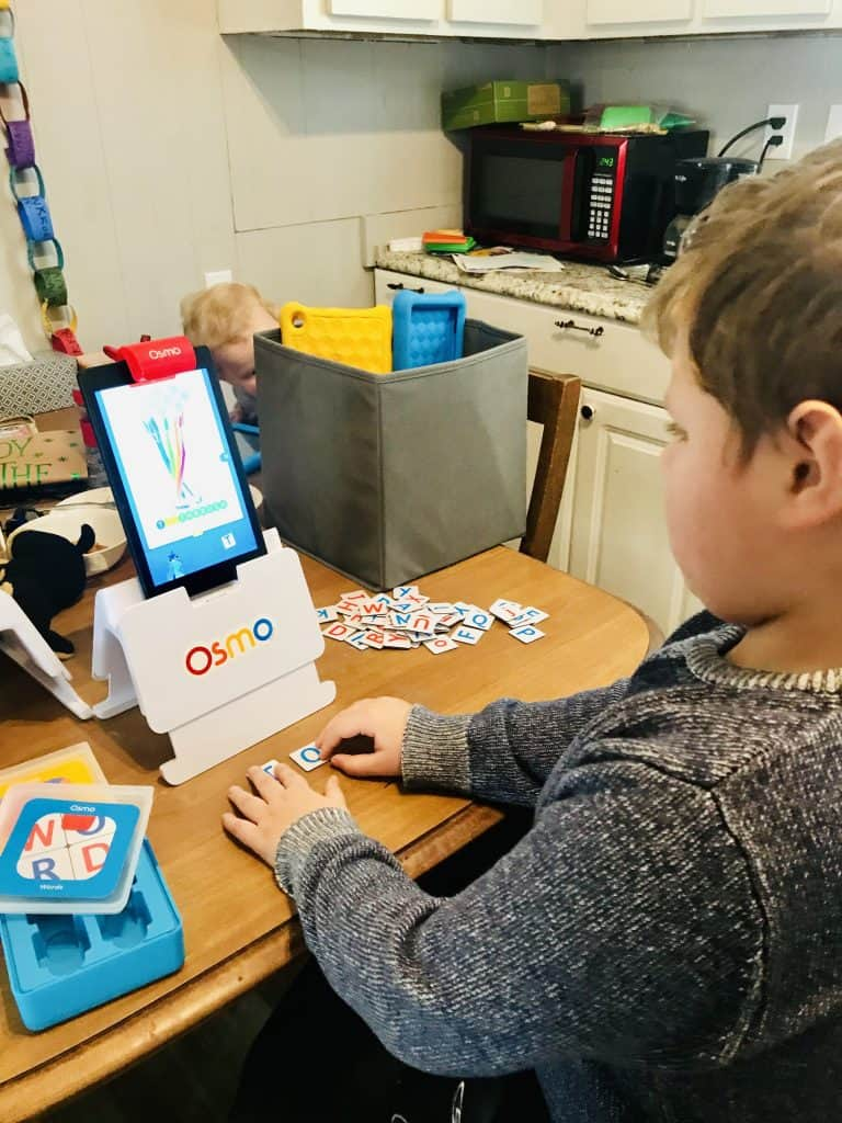 Boy playing Osmo numbers game with hands-on number pieces.