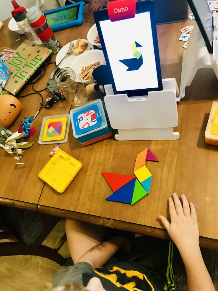 Boy playing Tangram Osmo Game on a Kindle Fire on a messy table.