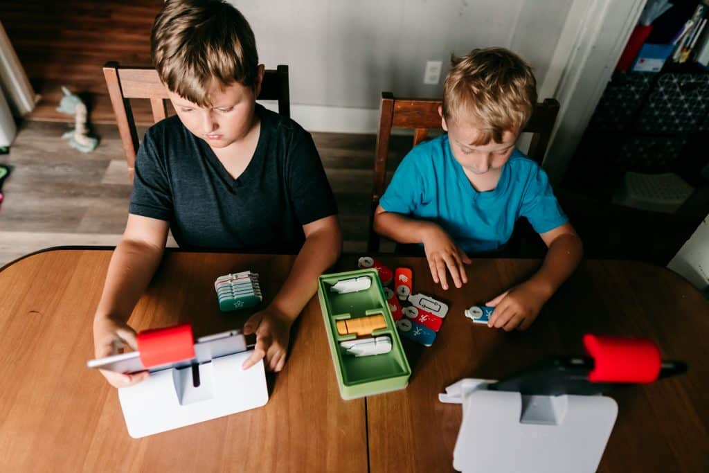 Two boys playing Osmo Coding Games at a kitchen table with hands-on game pieces and tablets on stands.
