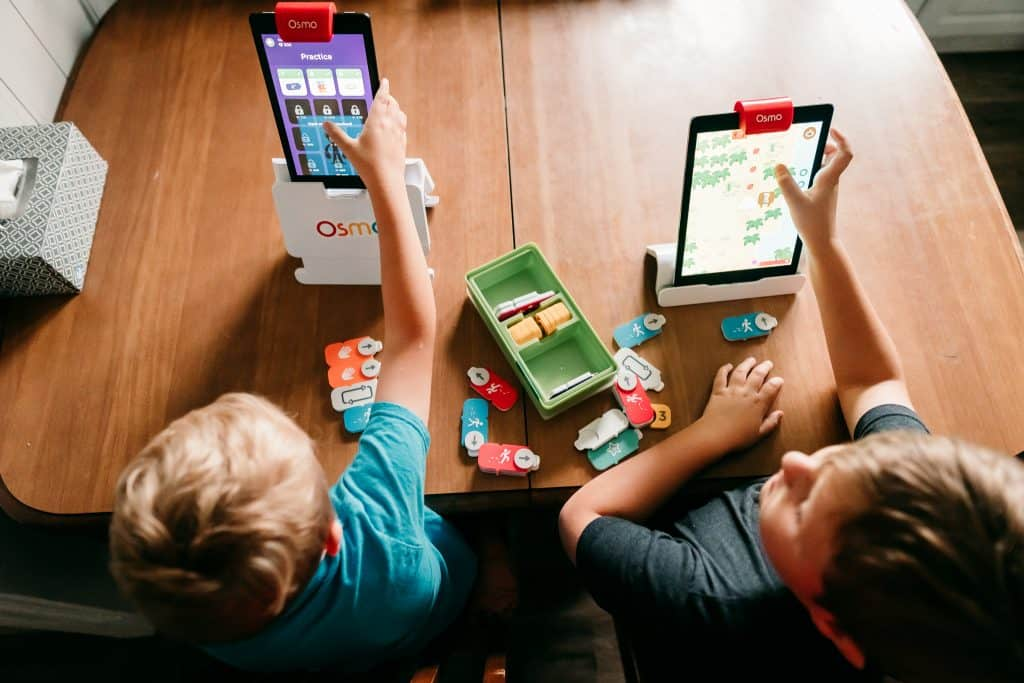 Two boys playing Osmo Coding games with hands-on game pieces at a kitchen table.