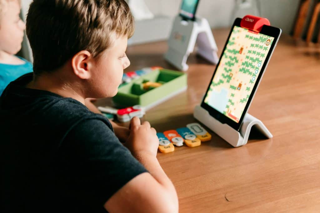 Boy playing Osmo Game Coding Awbie with hands-on game pieces and an iPad on stand.