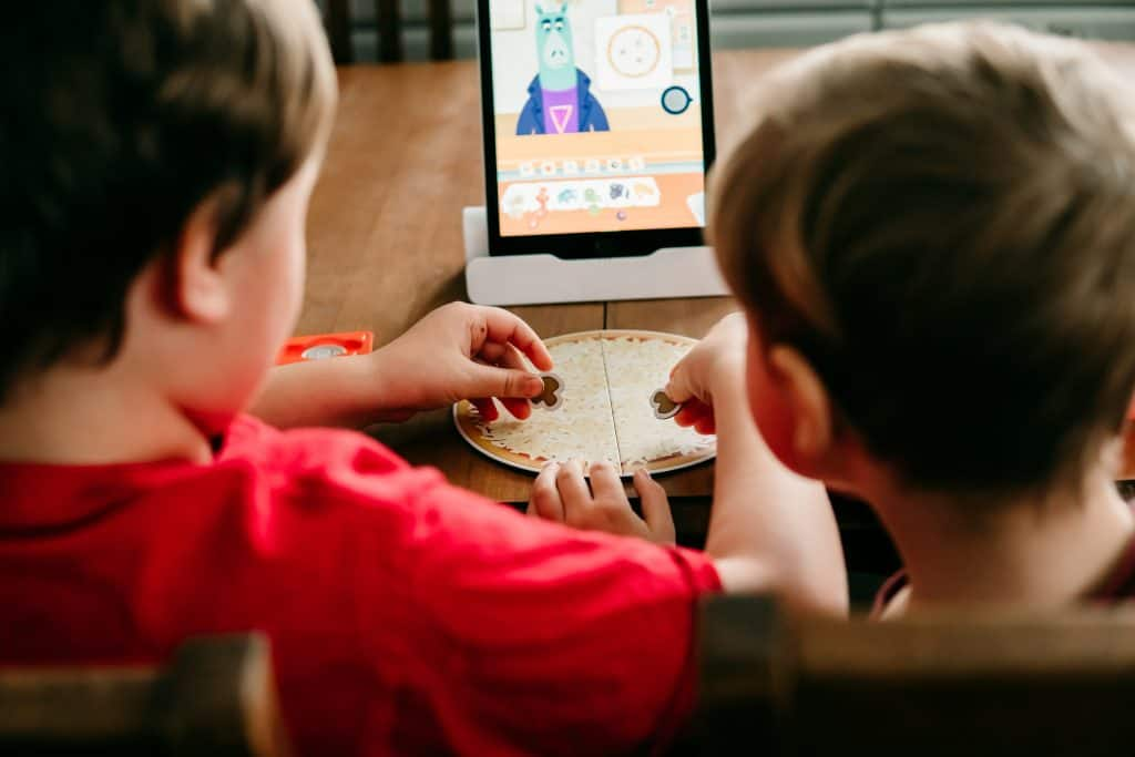 Two boys playing Osmo Pizza Co game on an iPad with hands-on game pieces.