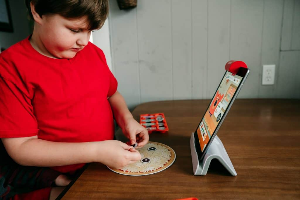 Boy playing Osmo Pizza Co game on an iPad with hands-on game pieces.
