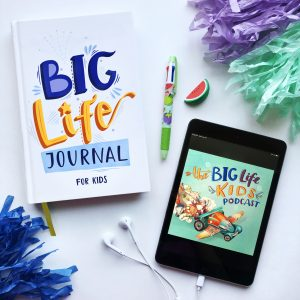 Big Life Journal laying on table with pencil and iphone with headphones
