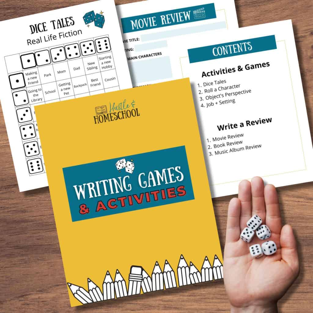 4 papers of writing games and activities sitting on a wood surface and a hand holding dice